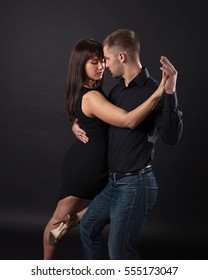 Young couple dancing on a dark background , studio shot
