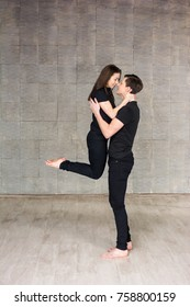 Young couple dancing on grey background. Young modern style couple dancing in romantic position on grey background.
