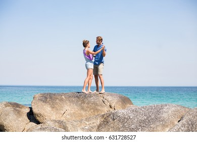 Young couple dancing on rock by sea against sky