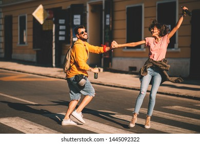 Young couple dancing on the street and holding two bottles of beer