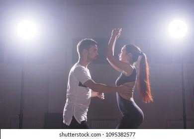 Young couple dancing social danse kizomba or bachata or semba or taraxia in dancing class background