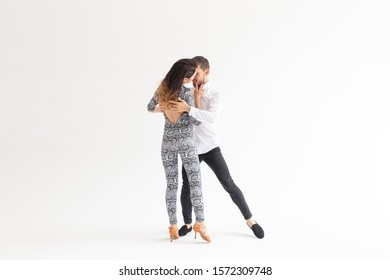 Young couple dancing social latin dance bachata, merengue, salsa. Two elegance pose on white background with copy space