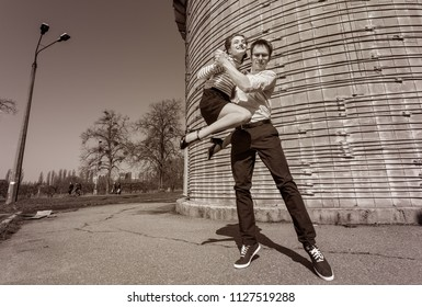young couple dancing swing outside somewhere on the street; black-and-white photo