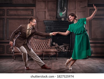 a young couple dancing swing in a retro hall in front of a fireplace and a leathern sofa; the woman wears a green dress