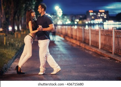 young couple dancing tango on the embankment of the river in the evening