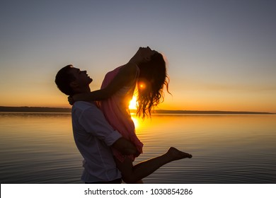 Young couple is dancing in the water on summer beach. Sunset over the sea.Two silhouettes against the sun. Just married couple is hugging. Romantic love story. Man and woman in holiday honeymoon trip.