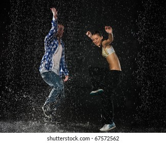 Young couple dancing in water under rain on a black background.  Modern dances.
