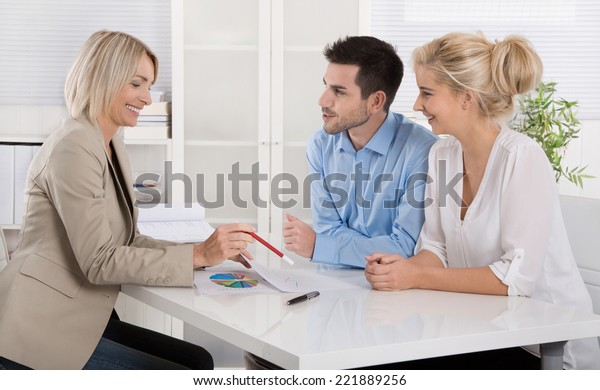 Young couple in a date with a banker or adviser for retirement arrangements.