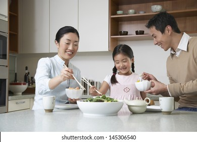 Young couple and daughter eating meal with chopsticks on kitchen counter