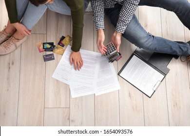 Young couple in debt at home, top view