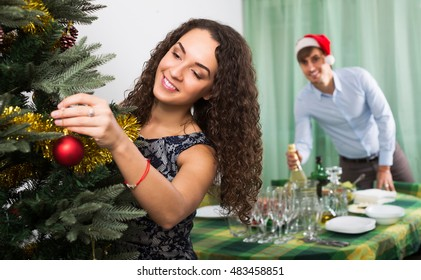 Young couple decorating Christmas tree and serving  festive table in home