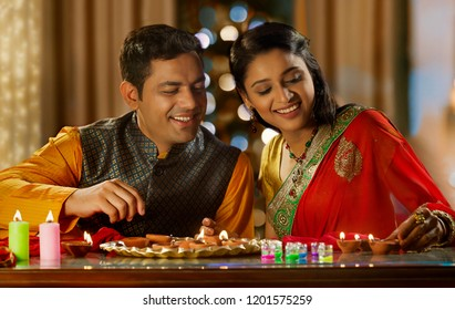 Young Couple decorating the house with diya on the occasion of Diwali