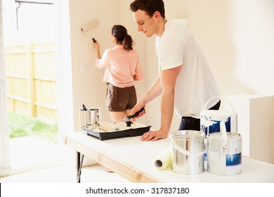Young couple decorating a room in their house