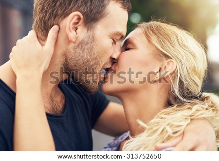 Young couple deeply in love sharing a romantic kiss, closeup profile view of their faces