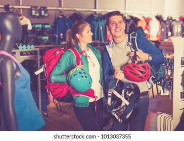 Young couple demonstrates the selected travel gear in sports shop