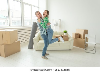 Young couple in denim pants embracing rejoicing in their new apartment during the move. The concept of housewarming and credit for new housing.
