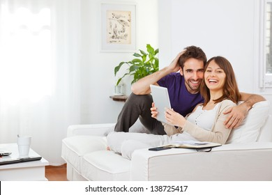 Young couple with digital tablet at home. Happy young couple smiling
