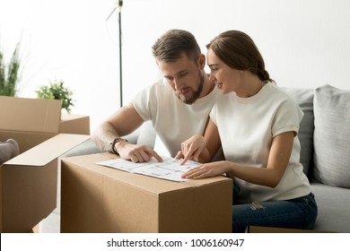 Young couple discussing house plan looking at blueprint just moved in new home with boxes, happy homeowners planning new apartment interior design and sharing furnishing remodeling ideas