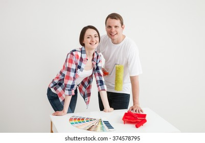 Young couple discussing a renovation of a home, neutral background