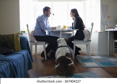 Young couple and dog eating breakfast