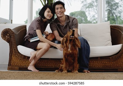 A young couple with a dog look at the camera