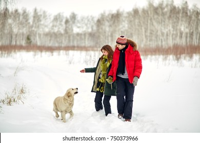 young couple with a dog on a winter walk. man and woman with labrador outdoors