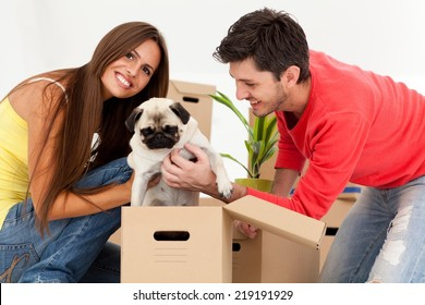 Young couple with dog surrounded by boxes moving into their new home.