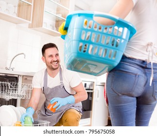 Young couple doing chores together. Man loading dishwasher and wife holding laundry basket