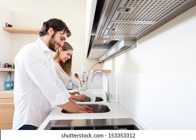 Young couple doing dishes in the kitchen