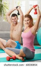 Young couple doing dumbbell exercise sitting on fittness mat at home, smiling.