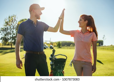 Young couple doing a high five on the golf coarse