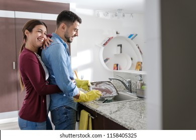 Young couple doing housework and chores. Man cleaning dishes in kitchen and girlfriend hugging him from behind