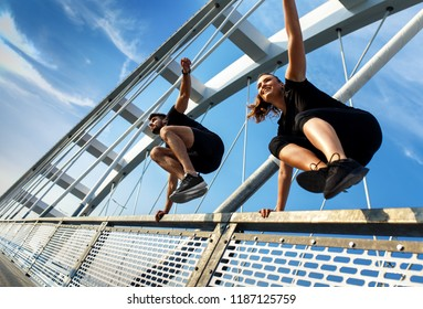 Young couple doing morning workout outdoor on bridge. Young man and woman jumping over the fence together.