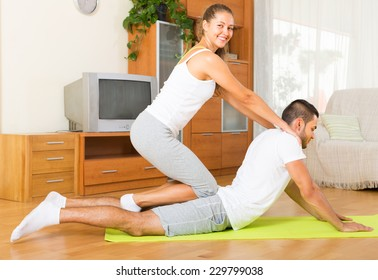 Young couple doing regular exercises together indoor