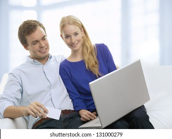 Young couple doing shopping in internet with credit card at home.