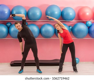 Young couple doing stretching exercises in a gym