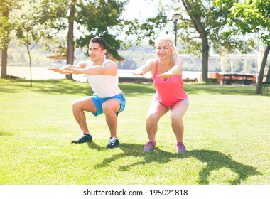 Young couple doing stretching exercises in the park