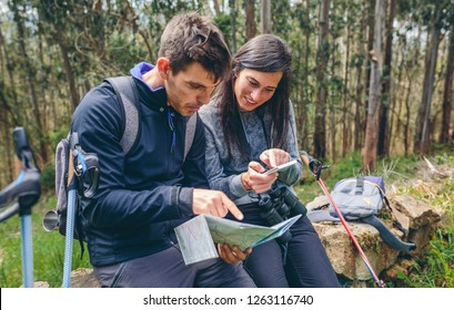 Young couple doing trekking sitting looking mobile and map outdoors