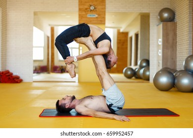 Young couple doing yoga at the gym on a yellow background