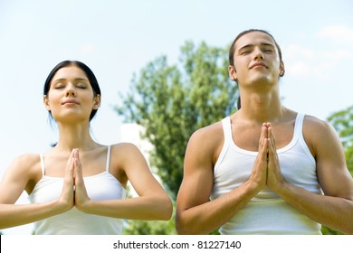 Young couple doing yoga moves, meditating or praying together, outdoors