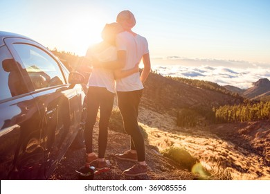Young couple dressed alike in white t-shirt and hat embracing near the car on the roadside on the sunset.