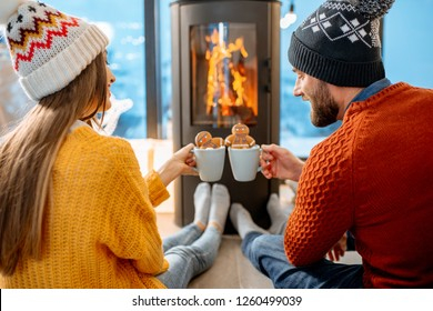 Young couple dressed in bright sweaters with hot drinks near the fireplace in the modern house in the mountains durnig winter time