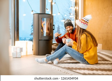 Young couple dressed in bright sweaters and hats sitting together near the fireplace in the modern house durnig winter time