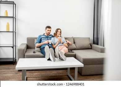 Young couple dressed casually sitting together on the couch and watching TV at home. Wide interior view