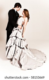 A young couple dressed in formal attire dancing affectionately with the man's arm around the woman's waist. The woman is wearing a white strapless dress and the man is wearing a suit. Vertical shot.