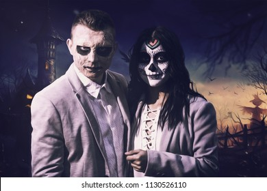 Young couple dressed up for halloween. Woman made up like Katrina and man disguised as a zombie. Disguised on dark background.