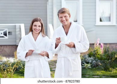 Young couple in dressing gowns with cups
