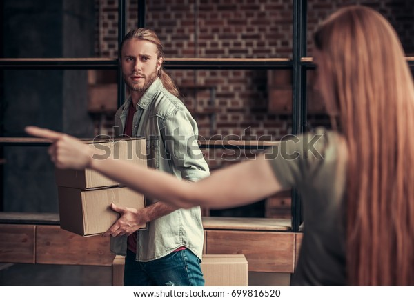 Young couple is drifting apart after breakup, girl is pointing to the entrance, man is carrying his stuff in cardboard boxes