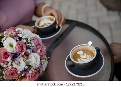 Young couple is drinking cofee. Two cups of cofee standing on the cofee table alongside with the flower pot closeup.