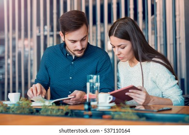 Young couple drinking coffee in the cafeteria and reading a book. Students, education, university, lifestyle concept